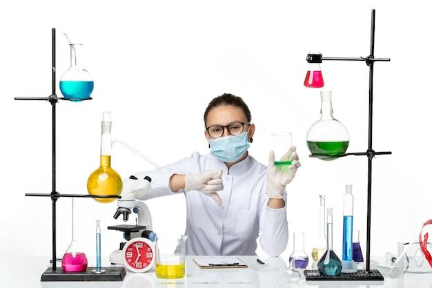 Widok z przodu kobieta chemik w garniturze medycznym z roztworem do przechowywania maski na jasnym białym tle plusk laboratorium wirus chemii covid-