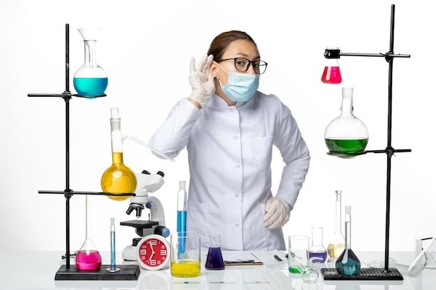 Widok Z Przodu Kobieta Chemik W Kombinezonie Medycznym Z Maską Próbuje Usłyszeć Na Białym Tle Laboratorium Chemii Wirusów Covid- Splash Darmowe Zdjęcia