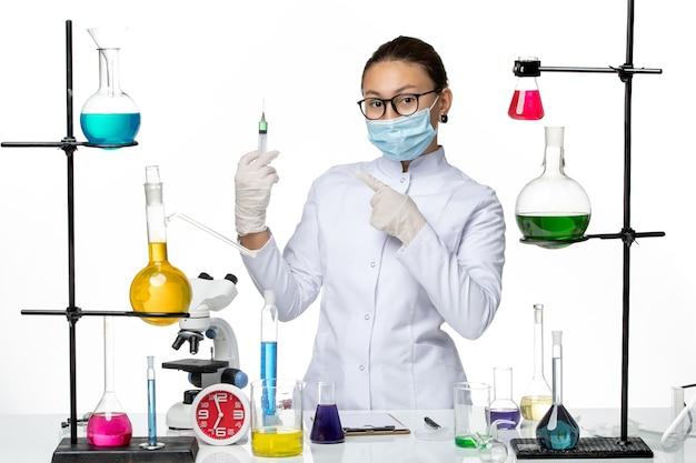 Widok z przodu kobieta chemik w kombinezonie medycznym z maską trzymającą zastrzyk na jasnym białym tle laboratorium chemii wirusa covid splash