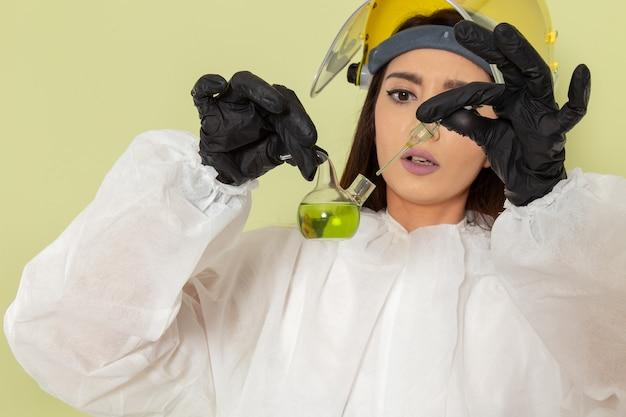Widok z przodu kobieta chemik w specjalnym ubraniu ochronnym, trzymająca kolbę z zielonym roztworem na zielonej powierzchni