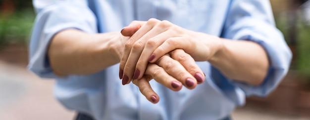 Widok z przodu kobieta dezynfekująca ręce na zewnątrz