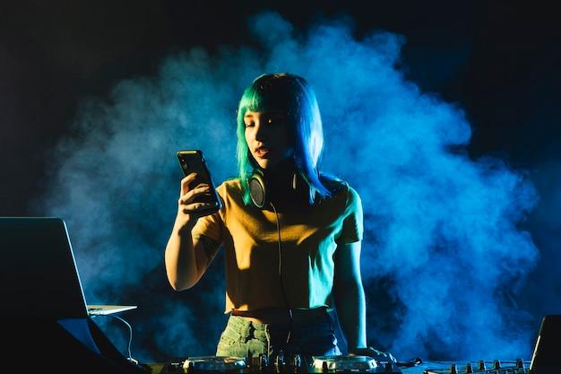 Widok z przodu kobieta dj sprawdzanie swojego telefonu