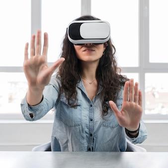Widok z przodu kobieta i zestaw słuchawkowy wirtualnej rzeczywistości