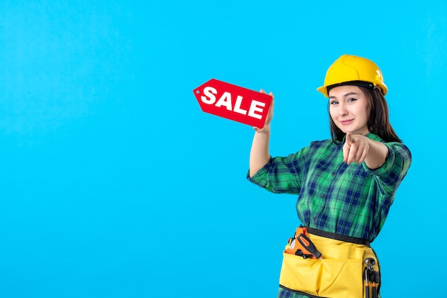 Widok z przodu kobieta konstruktor trzymająca czerwoną wyprzedaż piszącą na niebiesko