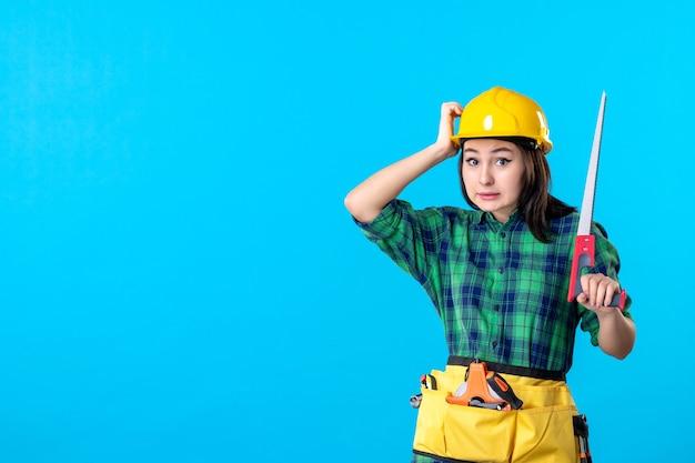 Widok z przodu kobieta konstruktor trzymająca małą piłę na niebieskim zadaniu konstruktor wieżowiec architektura budynków pracownik