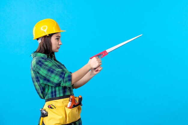Widok z przodu kobieta konstruktor trzymająca małą piłę na niebiesko