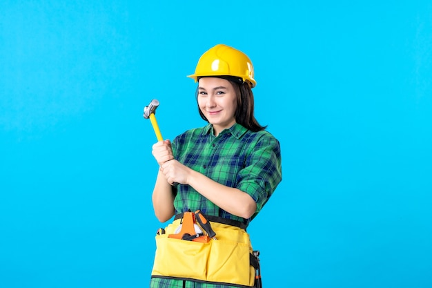 Widok z przodu kobieta konstruktor w mundurze trzymająca młotek na niebiesko