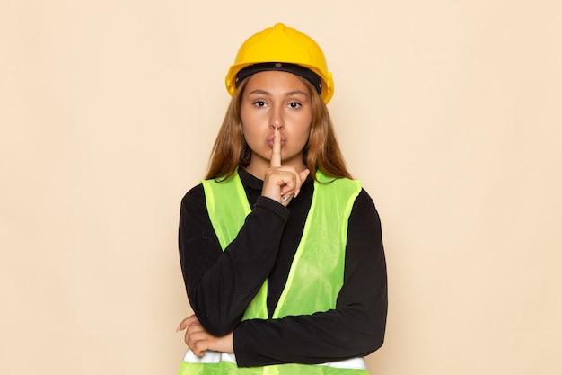 Widok z przodu kobieta konstruktor w żółtym hełmie czarnej koszuli pozuje pokazując znak ciszy na białej ścianie