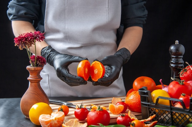 Widok z przodu kobieta kucharz cięcie mandarynki na ciemnym gotowanie sałatka zdrowie dieta warzywo posiłek jedzenie owoce praca