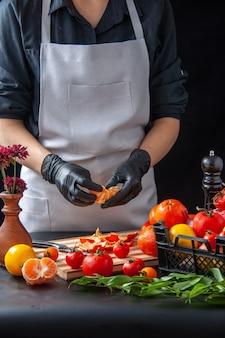 Widok z przodu kobieta kucharz czyszczenie mandarynek na ciemnym gotowaniu sałatka zdrowie dieta warzywny posiłek jedzenie praca