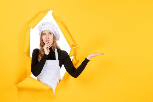 Widok z przodu kobieta kucharz myśli na żółtym zdjęciu słońce kuchnia praca kolor kuchnia papier spożywczy