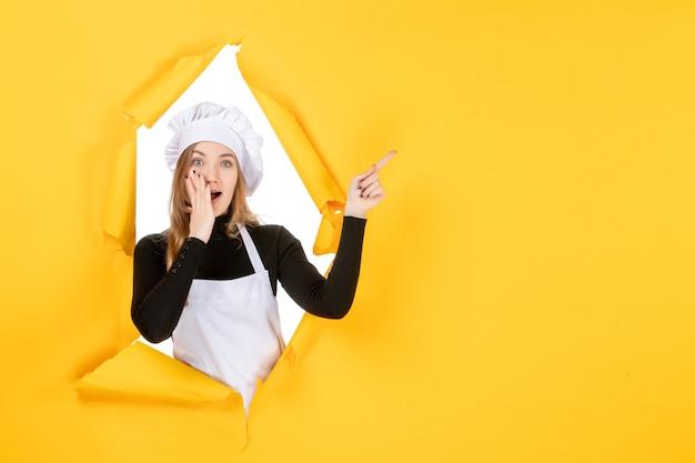 Widok z przodu kobieta kucharz na żółtym papierze spożywczym słońce emocja kuchnia praca kolor papieru