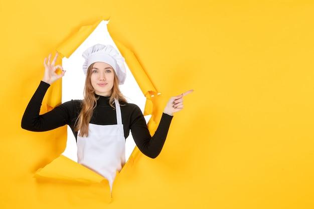 Widok z przodu kobieta kucharz na żółtym zdjęciu kuchennym jedzenie kuchnia praca kolor papieru