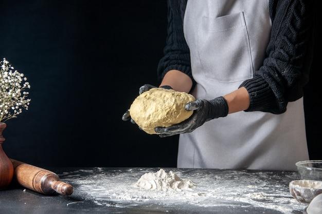 Widok z przodu kobieta kucharz trzyma ciasto na ciemnym cieście jajko praca piekarnia ciastko ciasto kuchnia kuchnia