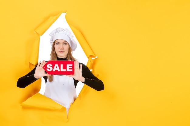 Widok z przodu kobieta kucharz trzyma czerwoną sprzedaż pisanie na żółtych pieniądzach kolor praca zdjęcie kuchnia kuchnia emocje jedzenie