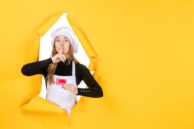 Widok z przodu kobieta kucharz trzymająca czerwoną kartę bankową na żółtej pracy zdjęcie emocja kuchnia kolor pieniądze kuchnia