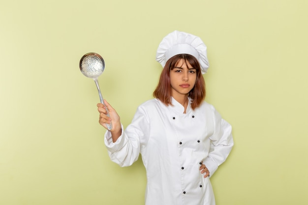 Widok z przodu kobieta kucharz w białym garniturze, trzymając dużą srebrną łyżkę na zielonej powierzchni