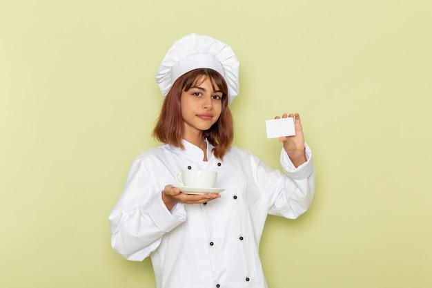 Widok z przodu kobieta kucharz w białym garniturze, trzymając filiżankę herbaty i kartę na zielonej powierzchni