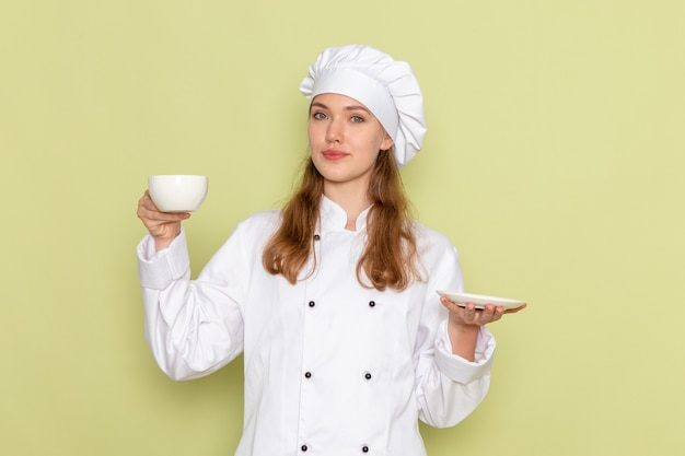 Widok z przodu kobieta kucharz w białym garniturze, trzymając kubek i talerz na zielonej ścianie