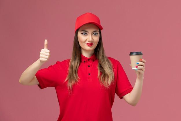 Widok z przodu kobieta kurier w czerwonym mundurze i pelerynie, trzymając filiżankę kawy dostawy na jasnoróżowym tle, świadczenie usług jednolite pracownik