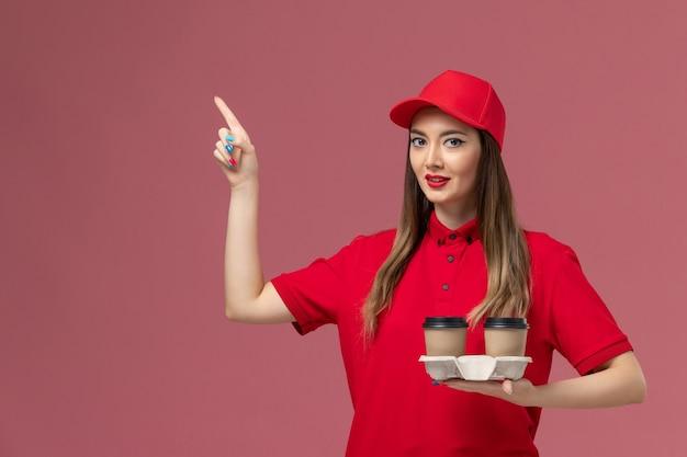 Widok z przodu kobieta kurier w czerwonym mundurze, trzymając brązowe filiżanki kawy dostawy na jasnoróżowym tle mundur dostawy pracy usługi