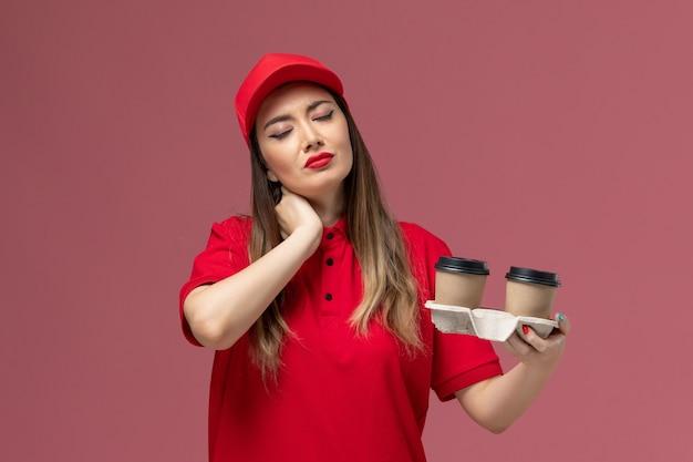 Widok z przodu kobieta kurier w czerwonym mundurze, trzymając brązowe filiżanki kawy dostawy na jasnoróżowym tle świadczenie usług jednolita firma pracy pracownika