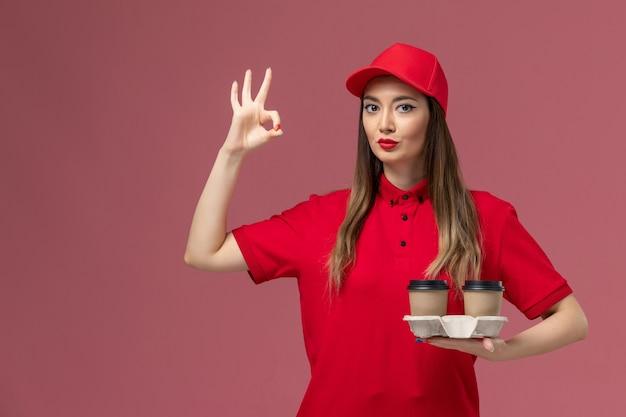 Widok z przodu kobieta kurier w czerwonym mundurze, trzymając brązowe filiżanki kawy dostawy pozowanie na różowym tle mundur dostawy pracy usługi