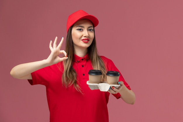 Widok z przodu kobieta kurier w czerwonym mundurze, trzymając brązowe filiżanki kawy dostawy uśmiechając się na jasnoróżowym tle dostawa usług jednolita praca pracownika firma kobieta