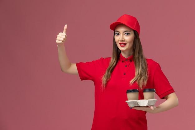 Widok z przodu kobieta kurier w czerwonym mundurze, trzymając brązowe filiżanki kawy dostawy, uśmiechając się na różowym tle mundur dostawy pracy usługi