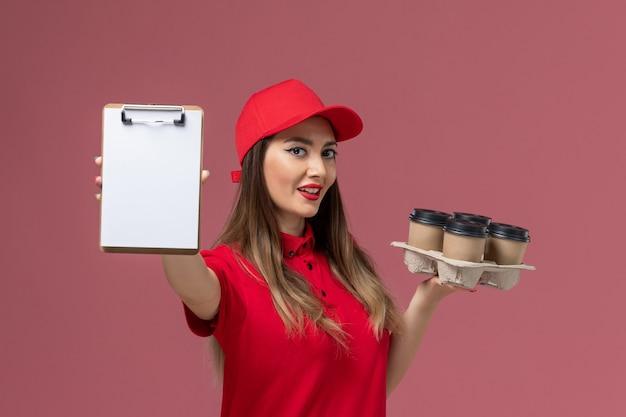 Widok z przodu kobieta kurier w czerwonym mundurze, trzymając dostawę filiżanek kawy notatnik na różowym tle mundur służbowy firmy usługowej