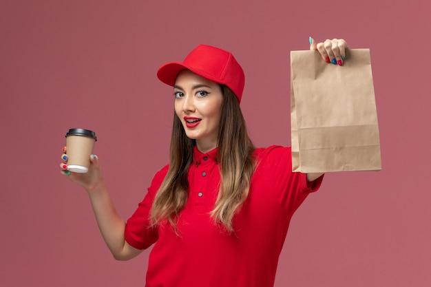 Widok z przodu kobieta kurier w czerwonym mundurze, trzymając dostawę filiżankę kawy i pakiet żywności na jasnoróżowym tle