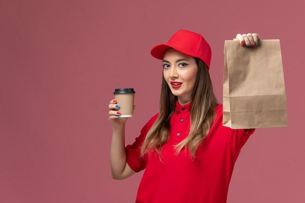 Widok z przodu kobieta kurier w czerwonym mundurze, trzymając dostawę filiżankę kawy i pakiet żywności na różowym tle dostawa usług pracownik mundurowy