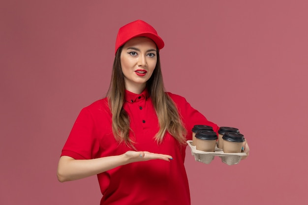 Widok z przodu kobieta kurier w czerwonym mundurze, trzymając filiżanki kawy dostawy na różowym tle świadczenie usług jednolity pracownik