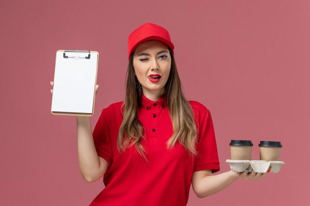Widok z przodu kobieta kurier w czerwonym mundurze, trzymając filiżanki z kawą dostawy i notatnik na jasnoróżowym tle