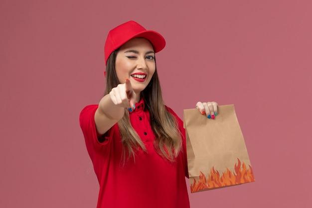 Widok z przodu kobieta kurier w czerwonym mundurze, trzymając papierowy pakiet żywności, mrugający na różowym tle, firma świadcząca usługi w mundurze