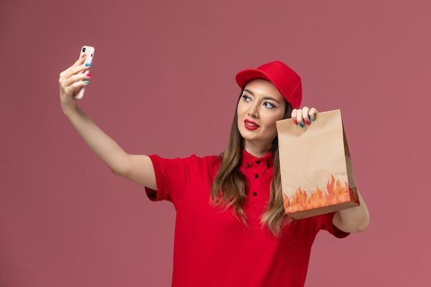Widok z przodu kobieta kurier w czerwonym mundurze, trzymając telefon i pakiet żywności, robiąc zdjęcie na różowym tle świadczenie usług mundurowy pracownik
