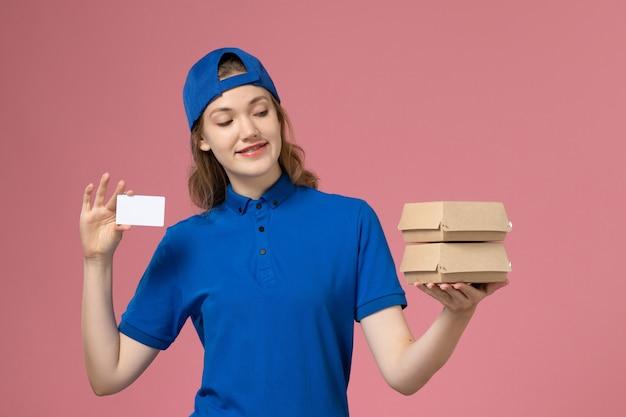 Widok z przodu kobieta kurier w niebieskiej pelerynie mundurowej trzymającej małe opakowania żywności dostawy i karty na różowym tle pracownik dostawy pracy