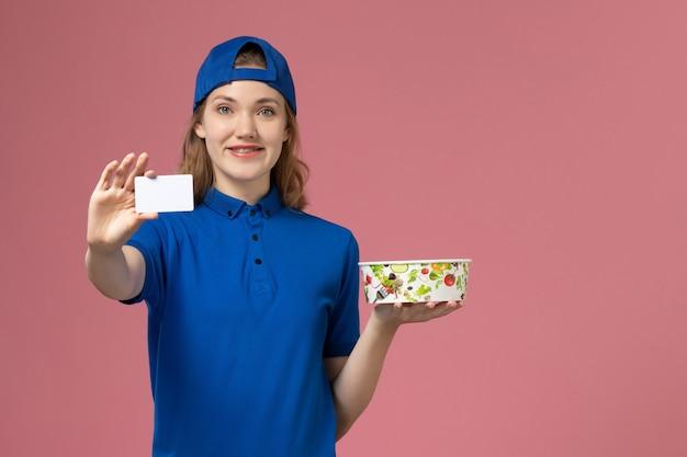 Widok z przodu kobieta kurier w niebieskiej pelerynie mundurowej trzymającej miskę dostawy z kartą na jasnoróżowej ścianie, dziewczyna pracownik dostawy usług