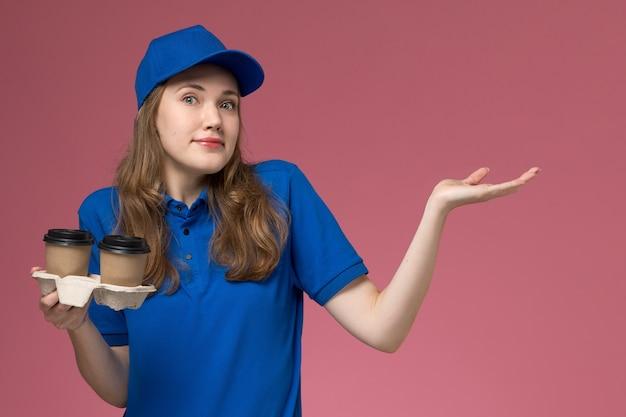Widok z przodu kobieta kurier w niebieskim mundurze, trzymając brązowe filiżanki kawy dostawy na różowym tle mundur usługowy dostarczający pracę firmy