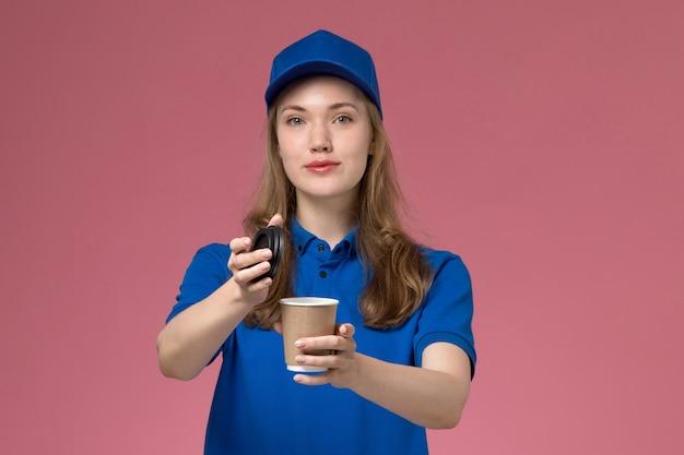 Widok z przodu kobieta kurier w niebieskim mundurze, trzymając brązowy kubek kawy, otwierając go na jasnoróżowym biurku jednolite stanowisko pracy firma dostarczająca