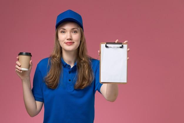 Widok z przodu kobieta kurier w niebieskim mundurze trzymając brązowy kubek kawy z notatnikiem na różowym tle mundur służbowy praca firma dostarczająca pracę