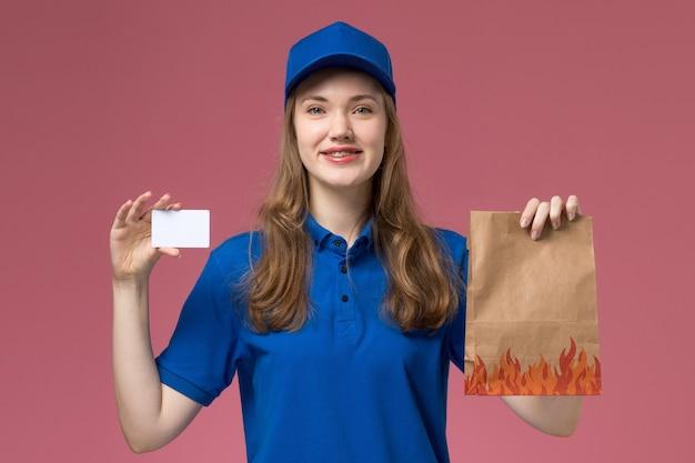 Widok z przodu kobieta kurier w niebieskim mundurze uśmiechnięta, trzymając białą kartę i pakiet żywności na różowym świetle biurka jednolita praca firmy