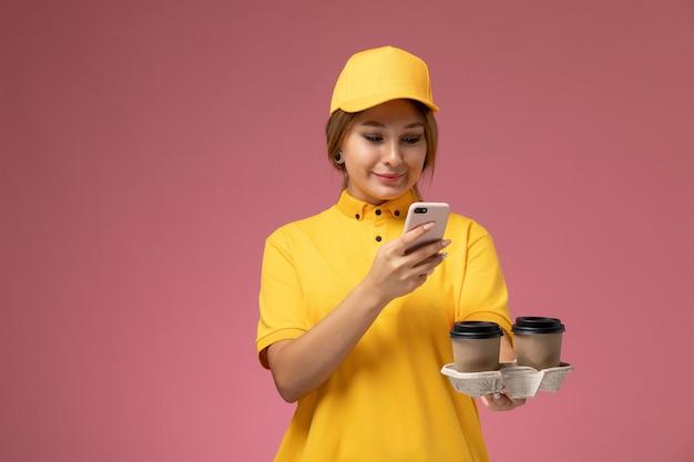 Widok z przodu kobieta kurier w żółtym mundurze żółtej pelerynie trzymającej filiżanki kawy za pomocą telefonu na różowym tle jednolita dostawa pracy kolor pracy