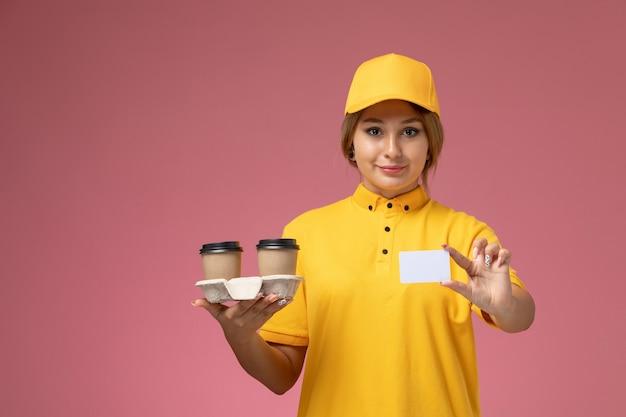 Widok z przodu kobieta kurier w żółtym mundurze żółtej pelerynie trzymającej kawę i białą kartkę na różowym tle jednolita dostawa pracy