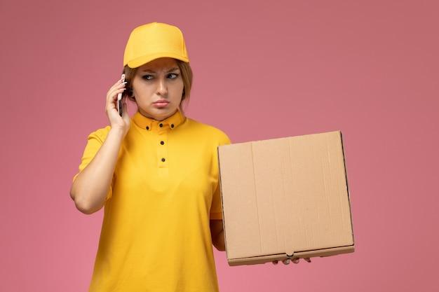 Widok z przodu kobieta kurier w żółtym mundurze żółtej pelerynie trzymającej pakiet dostawy rozmawia przez telefon na różowym tle jednolita praca przy dostawie