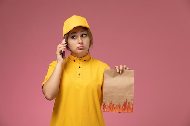 Widok z przodu kobieta kurier w żółtym mundurze żółtej pelerynie trzymającej pakiet żywnościowy rozmawia przez telefon na różowym tle jednolita dostawa pracy kolor pracy