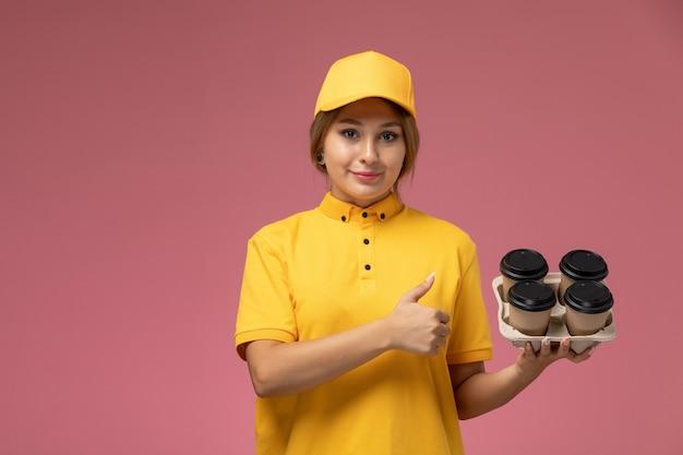 Widok z przodu kobieta kurier w żółtym mundurze żółtej pelerynie trzymającej plastikowe kubki do kawy uśmiechnięta na różowym tle jednolita dostawa pracy kolor pracy