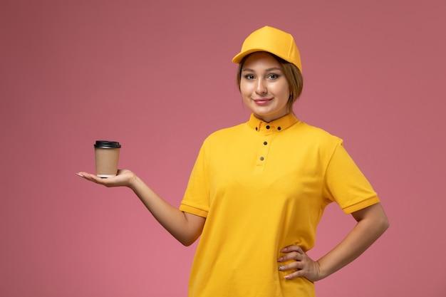 Widok z przodu kobieta kurier w żółtym mundurze żółtej pelerynie trzymającej plastikowy kubek z kawą z uśmiechem na różowym tle jednolita praca dostawy