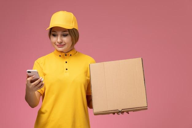 Widok z przodu kobieta kurier w żółtym mundurze żółtej pelerynie za pomocą pakietu dostawy telefonu na różowym tle jednolita praca dostawy