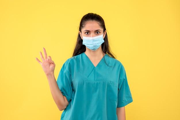 Widok z przodu kobieta lekarz pokazując trzy palce w pozycji stojącej